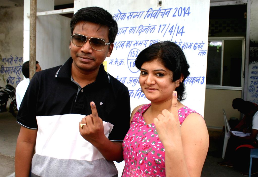 People show their fore fingers marked with phosphoric ink after casting their votes during the fifth phase of 2014 Lok Sabha Polls in Bhopal on April 17, 2014. Elections are being held in 117 ...
