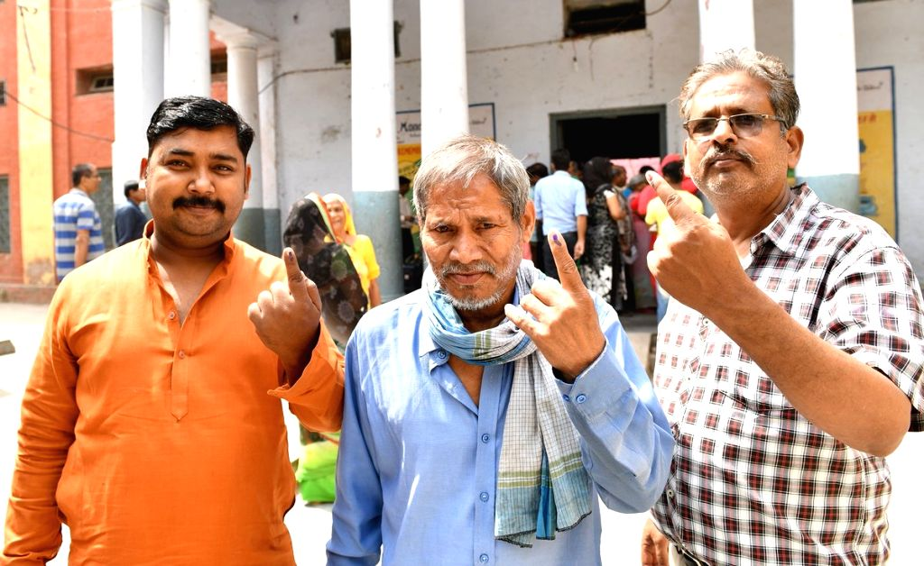 People show their forefingers marked with indelible ink after casting vote during the sixth phase of 2019 Lok Sabha elections, in Sadar Bazar of New Delhi on May 12, 2019.
