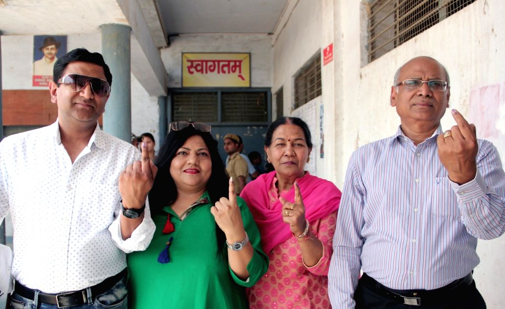 People show their inked fingers after casting their votes for the first phase of 2019 Lok Sabha elections, in Uttar Pradesh's Ghaziabad, on April 11, 2019.
