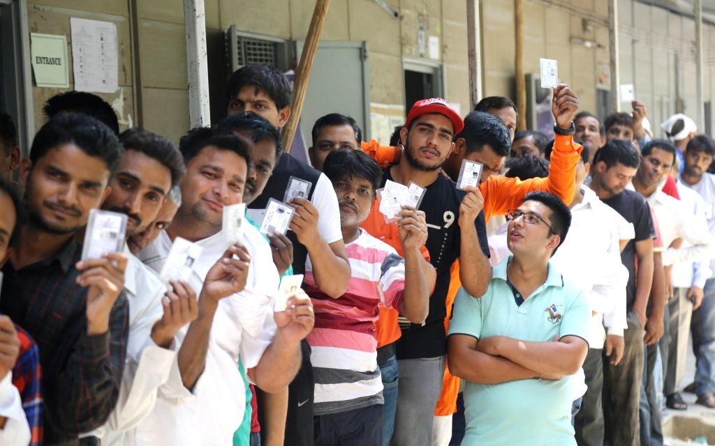 People show their voter identity card at a polling booth during the sixth phase of 2019 Lok Sabha elections, in New Delhi on May 12, 2019.