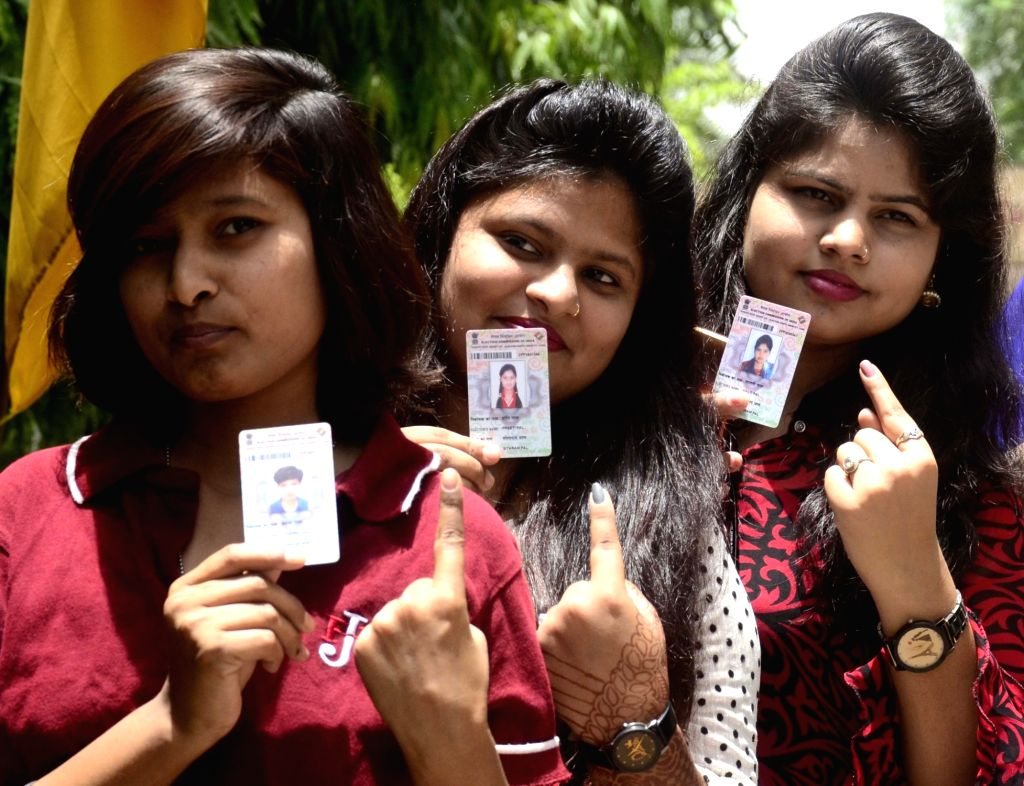 People show their voter identity card at a polling booth during the sixth phase of 2019 Lok Sabha elections, in Bhopal on May 12, 2019.