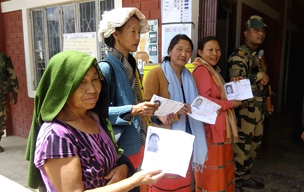 People show their voter slips as they arrive to cast their votes for the first phase of 2019 Lok Sabha elections, at a polling booth in Manipur, on April 11, 2019.