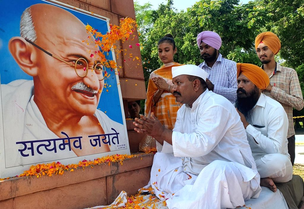 People shower  over a portrait of Mahatma Gandhi on the occasion of the 152nd birth anniversary of the 'Father of the Nation' Mahatma Gandhi, in Amritsar on Saturday October 02, 2021.