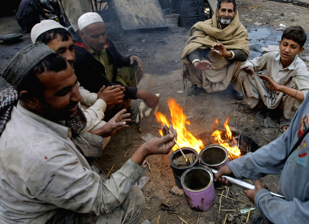 People sit around a fire to warm themselves during a cold day in northwest Pakistan's Peshawar, Dec. 8, 2015.