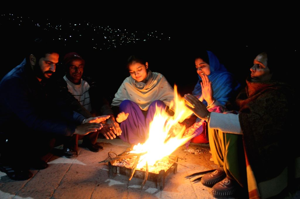 People sit around the fire as they warm themselves on a chilly winter evening in Shimla on Dec 10, 2018.
