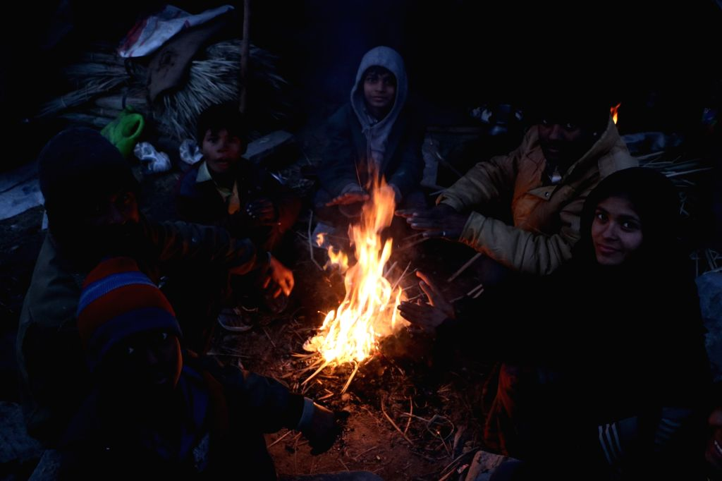 People sit around the fire to warm themselves on a cold day at Jammu Srinagar National Highway, on Dec 10, 2018.