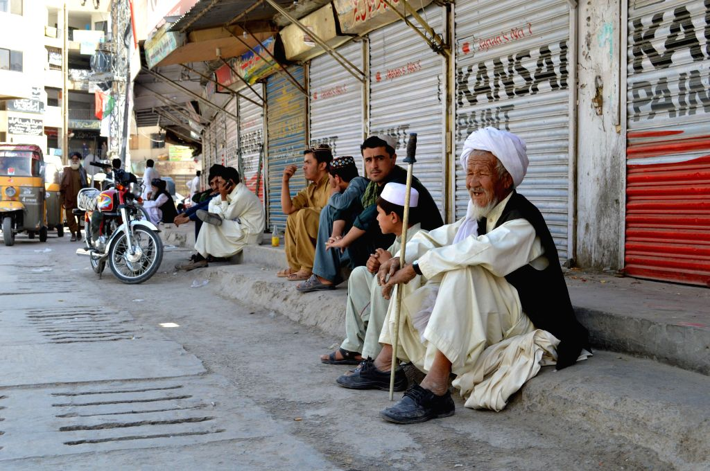 People sit in front of closed shops at a market during a traders' strike in southwest Pakistan's Quetta, Aug. 5, 2015. Traders in major cities of the country ...