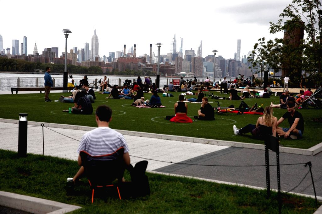 People sit in social distancing markers at Domino Park in New York, the United States, Sept. 13, 2020. The total number of COVID-19 cases in the United States ...