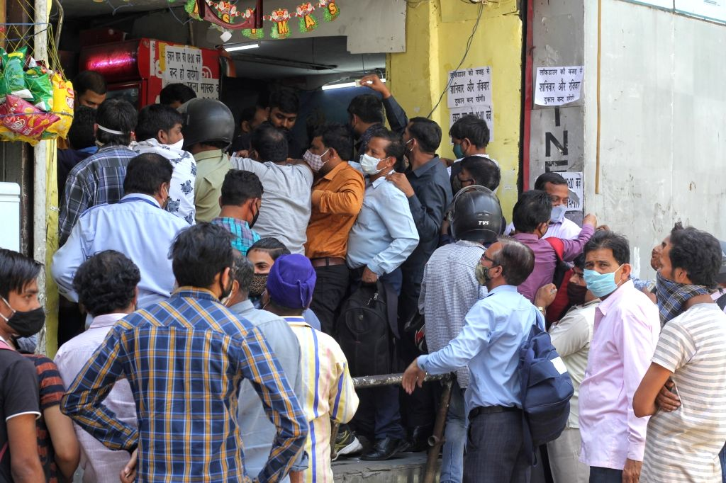 People stand in a que for buying wine at a wine shop backside of Regal building CP after Delhi CM Arvind Kejriwal announce one week Lockdown in new Delhi On Monday, 19th 2021. - Arvind Kejriwal