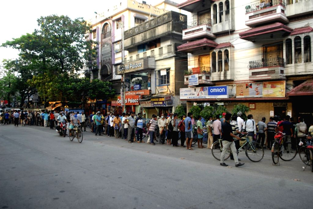 People stand in a queue at a liquor store, due to lockdown started from tomorrow during coronavirus pandemic in Kolkata on Saturday, 15 May, 2021.