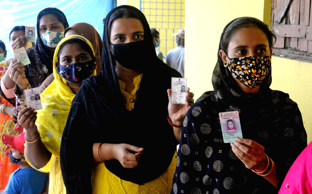 People stand in a queue at a polling station to cast their vote during the 5th phase of West Bengal's State Assembly elections at Barasat in North 24 Parganas on Saturday, 17th April, 2021.