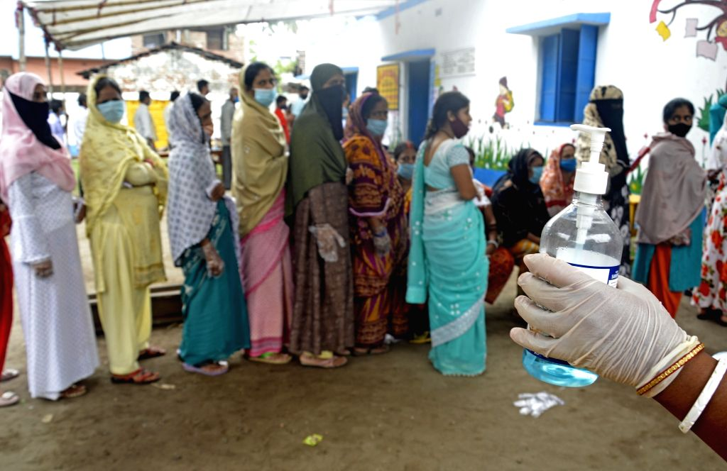 People stand in a queue at a polling station to cast their vote during the 6th phase of West Bengal's State Assembly elections at Barrackpore constituency in North 24 Parganas