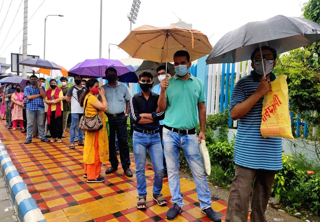 People stand in a queue for vaccination in the rain at Kishore Bharati Stadium during the coronavirus pandemic in Kolkata on Tuesday June 15, 2021.