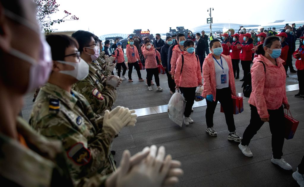 People stand in line to see off medics supporting virus-hit Hubei Province at Wuhan Tianhe International Airport in Wuhan, central China's Hubei Province, March 18, ...