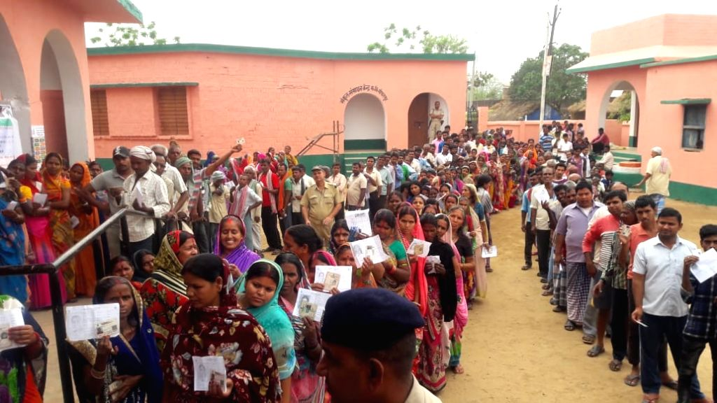 People stand in queue to cast vote for Lok Sabha election at a polling station, in Bihar's Jamui, on April 11, 2019.