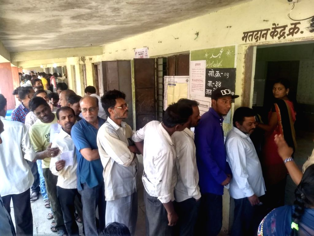 People stand in queue to cast vote for Lok Sabha election at a polling station, in Washim, Maharashtra, on April 11, 2019.