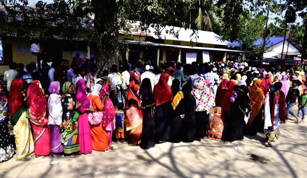 People stand in queue to cast vote for Lok Sabha election at a polling station in Assam's Nagaon district, on April 11, 2019.