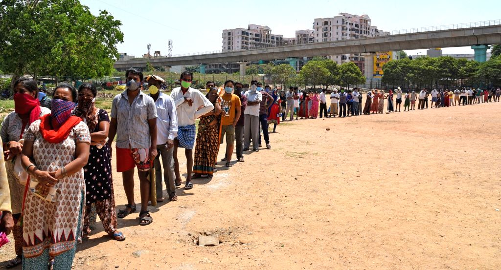 People stand in queues to collect vegetables being distributed free of cost among the poor, needy and homeless people in Bengaluru during the extended nationwide lockdown imposed to ...