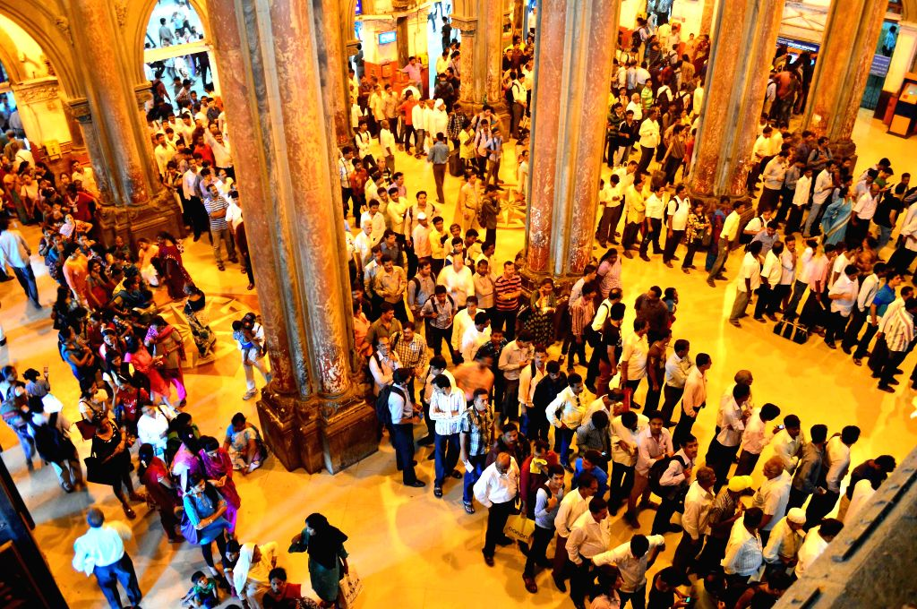 People stand in serpentine queues to renew their monthly travelling passes at Chhatrapati Shivaji Terminus (CST) in Mumbai on June 24, 2014.