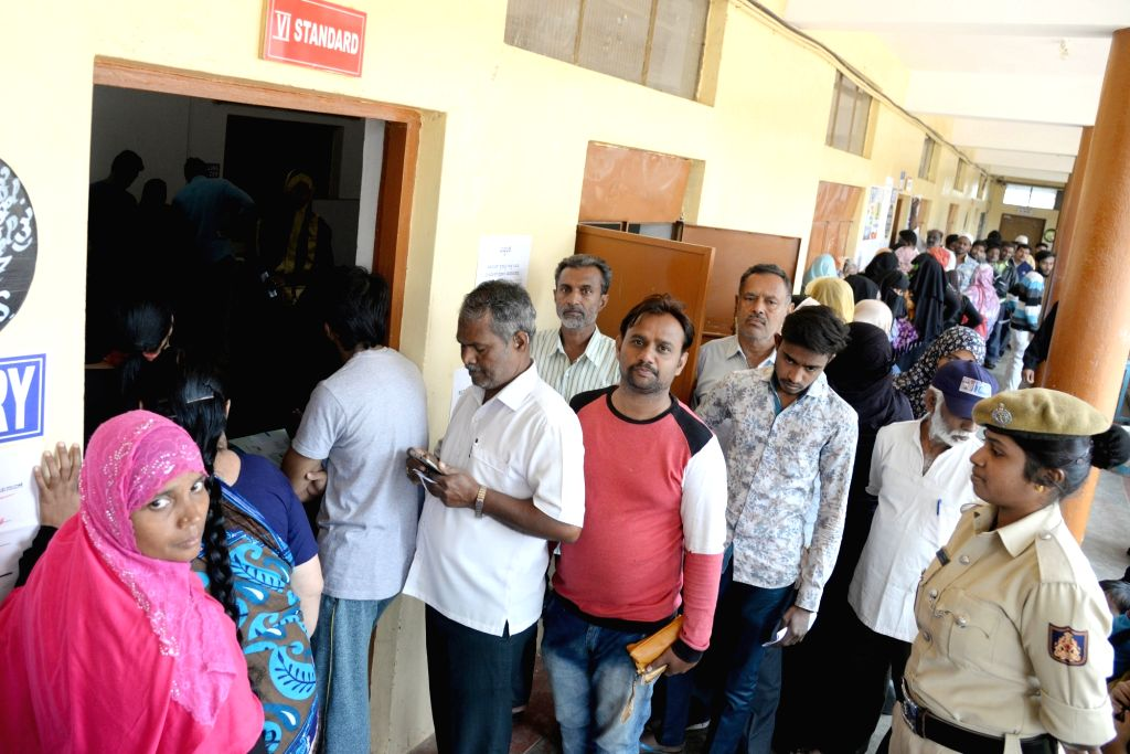 People stand in the queue at Yeshwantha Pura constituency to cast their vote for Karnataka bye-polls in Bengaluru on Dec 5, 2019.