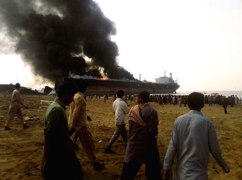 People stand near a burning ship at the explosion site in southwest Pakistan's Hub, Nov. 1, 2016. At least 10 laborers were killed and over 50 others injured in an ...