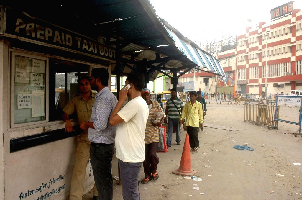 People stand outside a vacant taxi booth as taxi drivers go on strike in Kolkata on Aug 7, 2014.