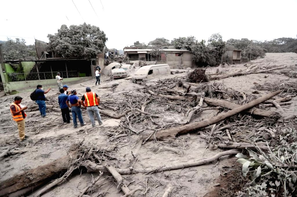 People stand with debris after the eruption of the Fuego volcano, in San Miguel Los Lotes, a village in Escuintla, Guatemala, on June 4, 2018. The death ...