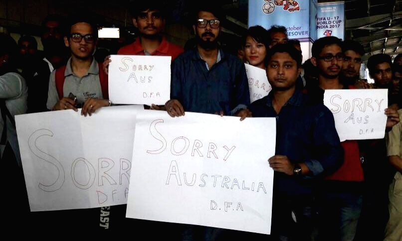 """People stand with placards reading """"Sorry Australia"""" at Lokpriya Gopinath Bordoloi International Airport in Guwahati on Oct 11, 2017. Australian cricket squad suffered a scare ..."""