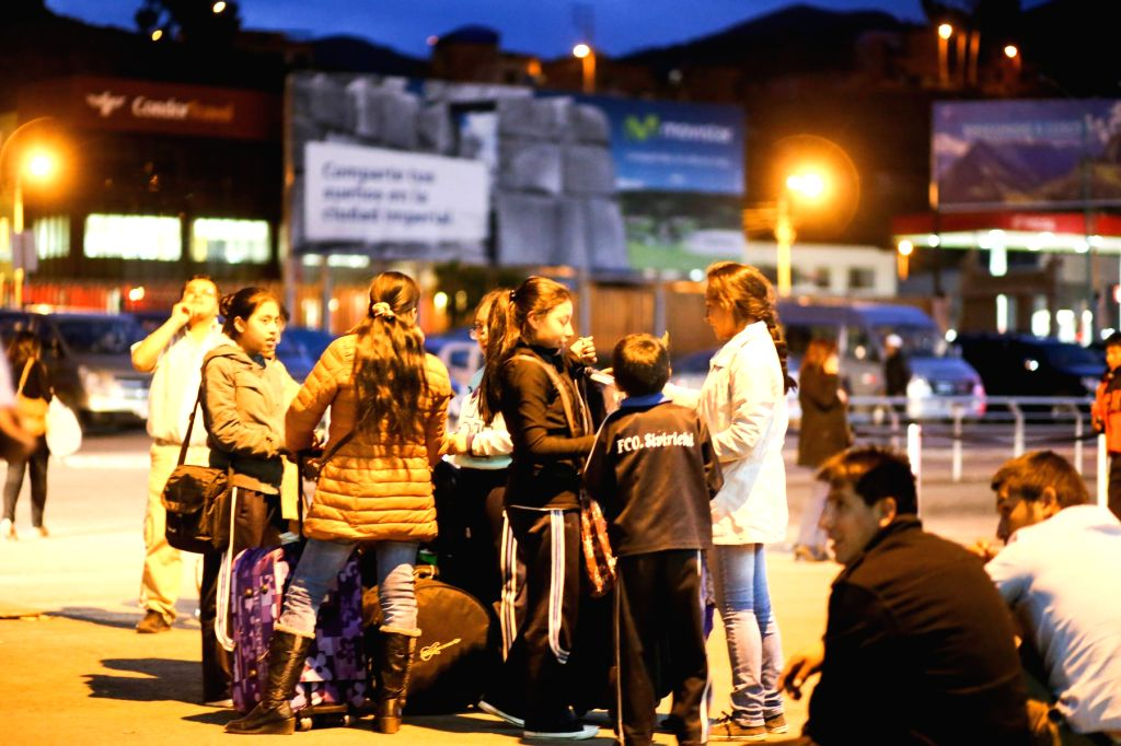 People stay on a street after an earthquake in the city of Cuzco, southeast of Peru, on Nov. 24, 2015. An earthquake measuring 7.7 on the Richter scale jolted Peru at ...