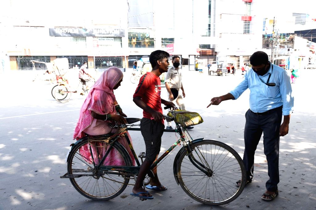 People stepping out of their homes without wearing masks being intercepted by the police during a re-imposed COVID-19 lockdown in Patna on July 16, 2020.