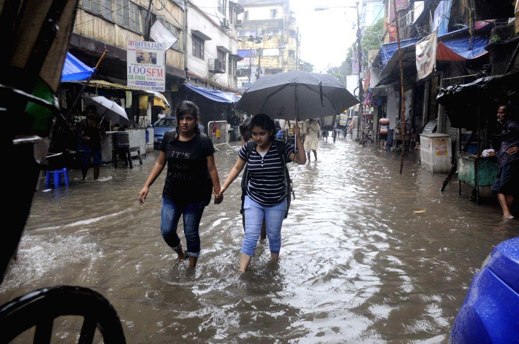 People struggle through a water-logged street during rains, in Kolkata on July 27, 2018.