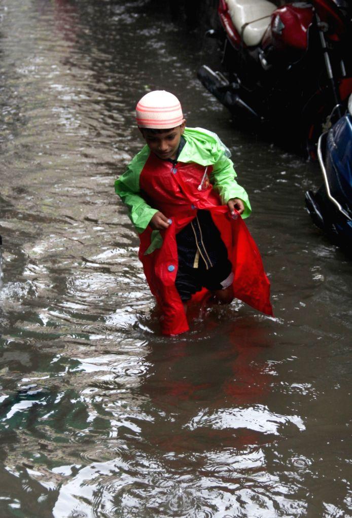 People struggle through the waterlogged streets after rains lash Kolkata, on Aug 1, 2018.