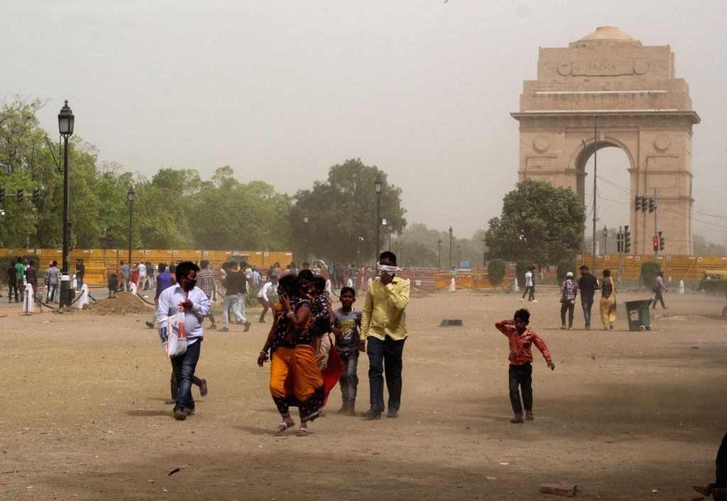 People stuck during the heavy dust storm at India Gate lawn in new Delhi on Monday March 30, 2021.