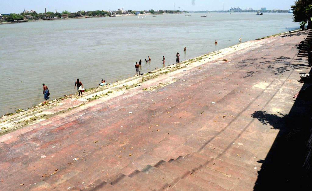 People take a bath in the Ganga river on Day 5 of the 21-day countrywide lockdown imposed to contain the spread of novel coronavirus, in Kolkata on March 29, 2020.