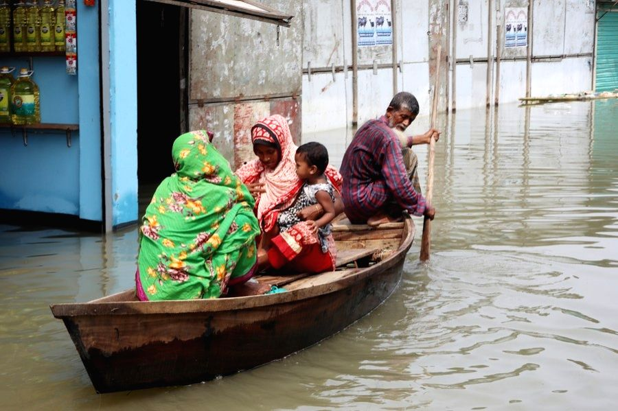 People take a boat in a flooded area in Munshiganj on the outskirts of Dhaka, capital of Bangladesh, on July 27, 2020.