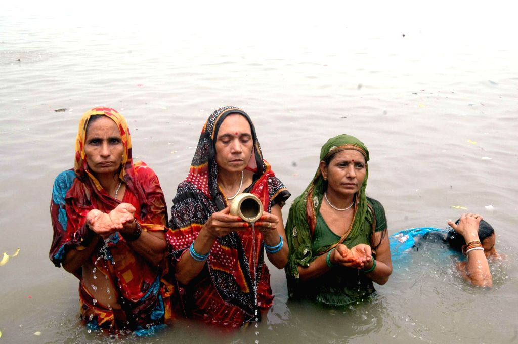 People take a holy dip in Ganga river on Somvati Amavasya in Patna on Aug 25, 2014.