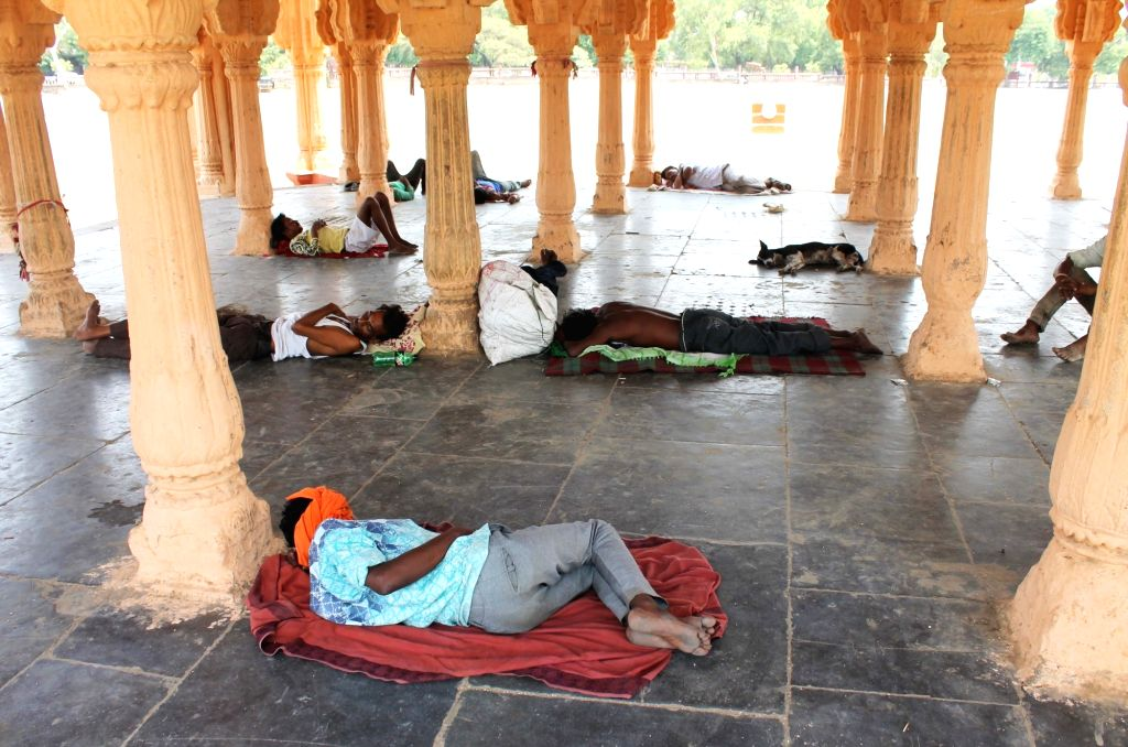 People take a nap under a bandstand at Kasturchand Park on a hot sunny day, in Nagpur on May 22, 2018.