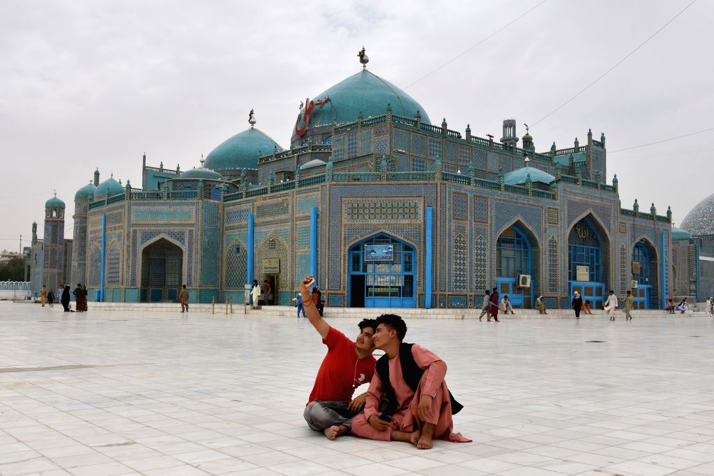 People take a selfie in front of the Blue Mosque in Mazar-i-Sharif, capital of Balkh province, northern Afghanistan, July 11, 2020. After a five-month shutdown due to ...