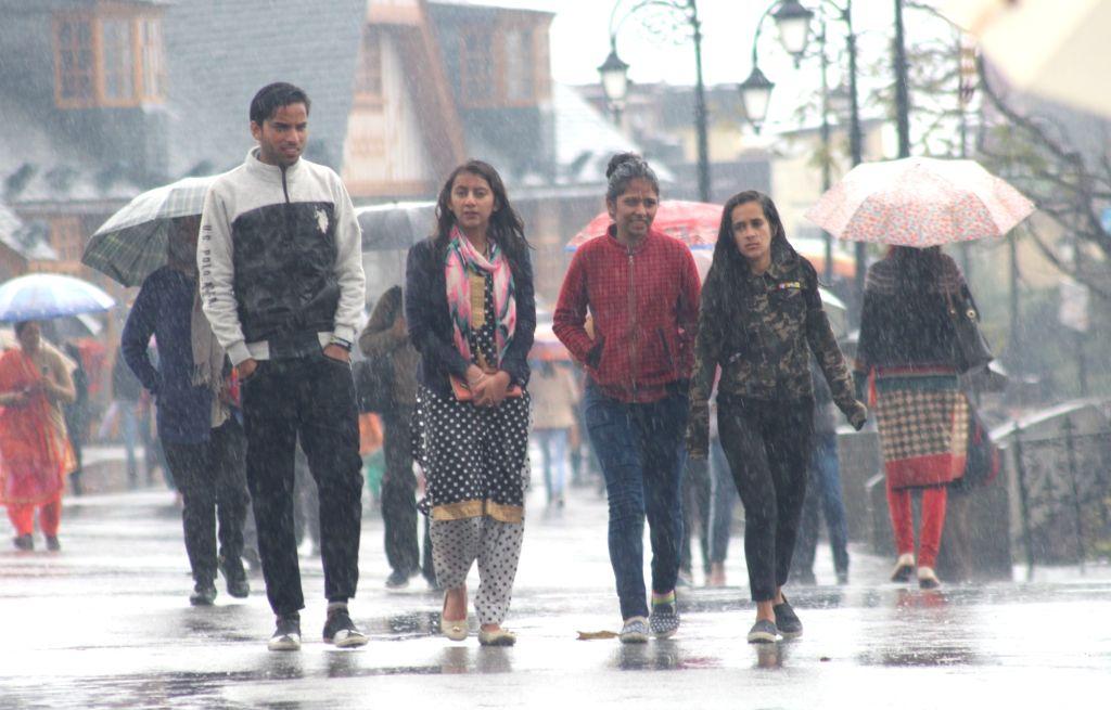 People take a stroll during rains in Shimla on Nov 3, 2018.