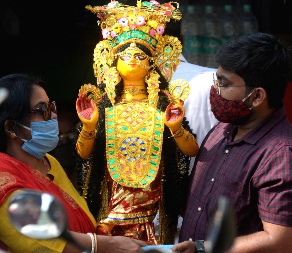 People take hoke idols of Goddess Laxmi on the eve of Laxmi Puja celebrations from Kumartuli workshop, in Kolkata on Oct 29, 2020.