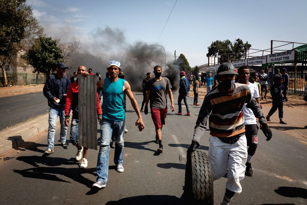 People take part in a protest over the death of a teenager in Eldorado Park, Johannesburg, South Africa, Aug. 27, 2020. South African President Cyril Ramaphosa ...