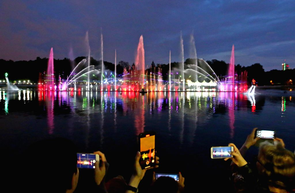 People take photos of a musical fountain in a river in Minsk, Belarus, July 3, 2020. After five months of construction, the musical fountain made its debut in Minsk on ...