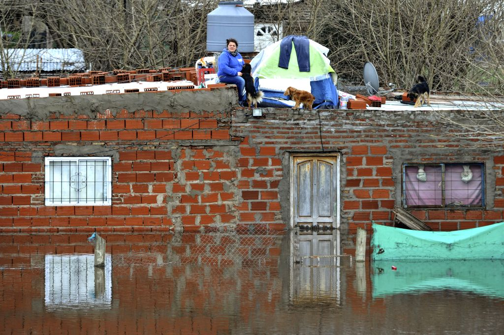 People take refuge from the flood at the roof of their house in Lujan city, Buenos Aires province, Argentina, on Aug. 11, 2015. According to local press, the heavy ...