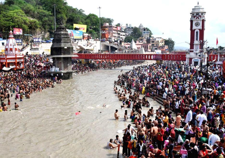 People throng Har Ki Pauri to take holy dip in the Ganga river on Somvati Amavasya in Haridwar on July 3, 2016.