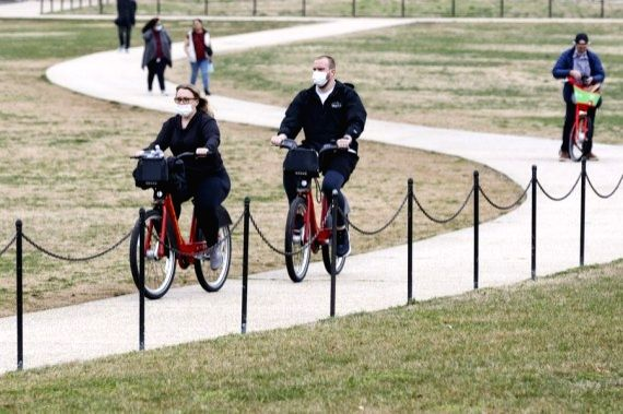 People tour the National Mall in Washington, D.C., the United States, on March 25, 2021.