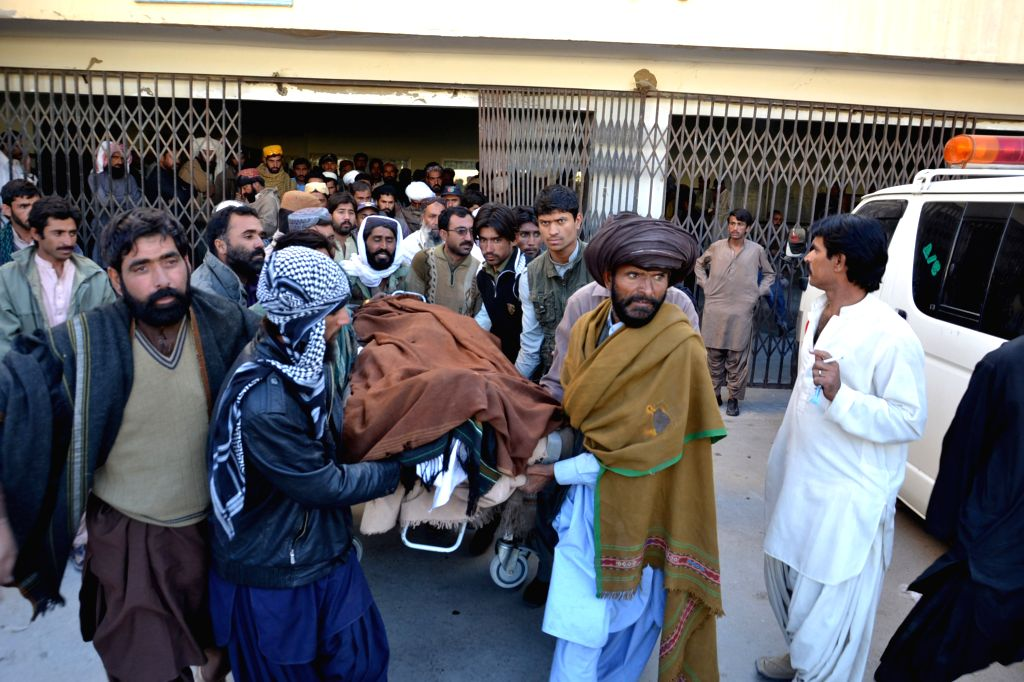 People transfer a body of a victim to a hospital in Quetta, Pakistan, Oct. 30, 2015. At least five people were killed and two others injured as a car struck an ...