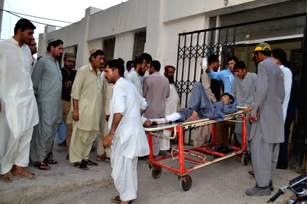 People transfer an injured boy to a hospital in southwest Pakistan's Quetta, Aug. 11, 2015. At least two policemen were killed and six other people were injured in a ...