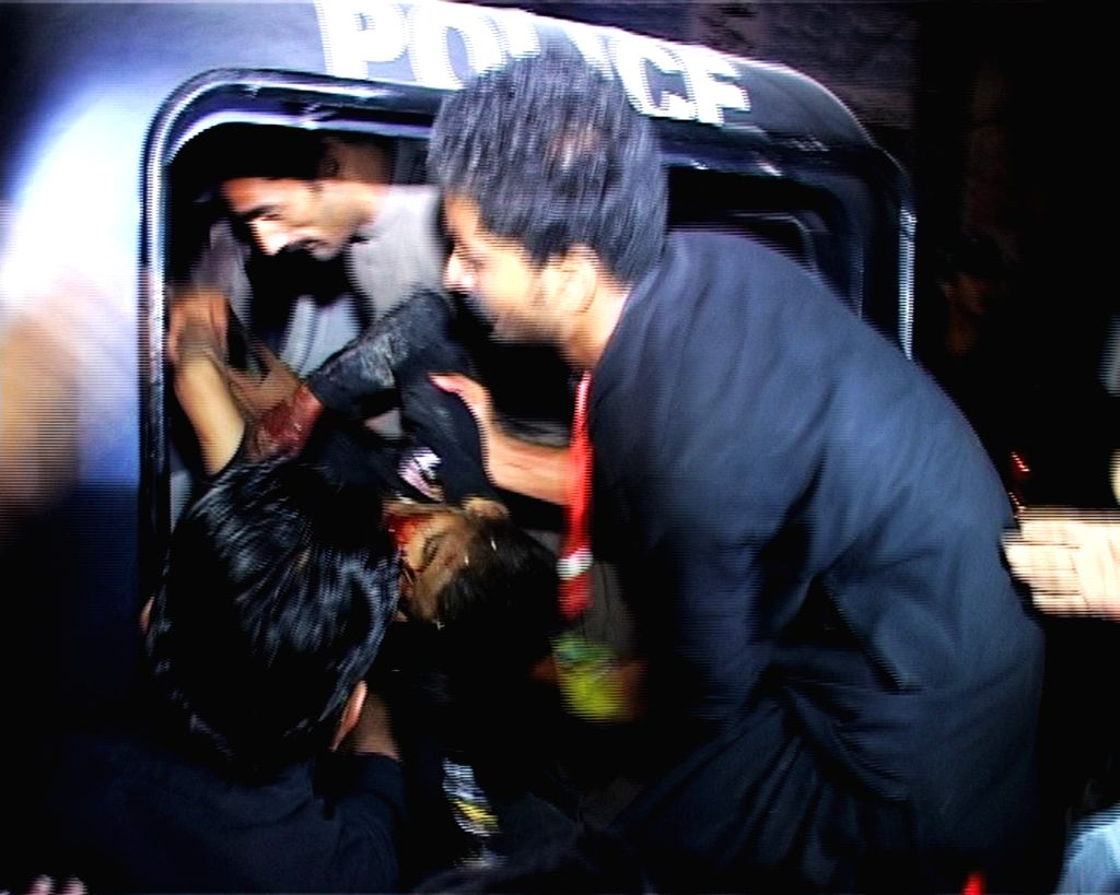 People transfer an injured man after a suicide blast in southwest Pakistan's Jacobabad on Oct. 23, 2015. At least 20 people including seven kids were killed and ...