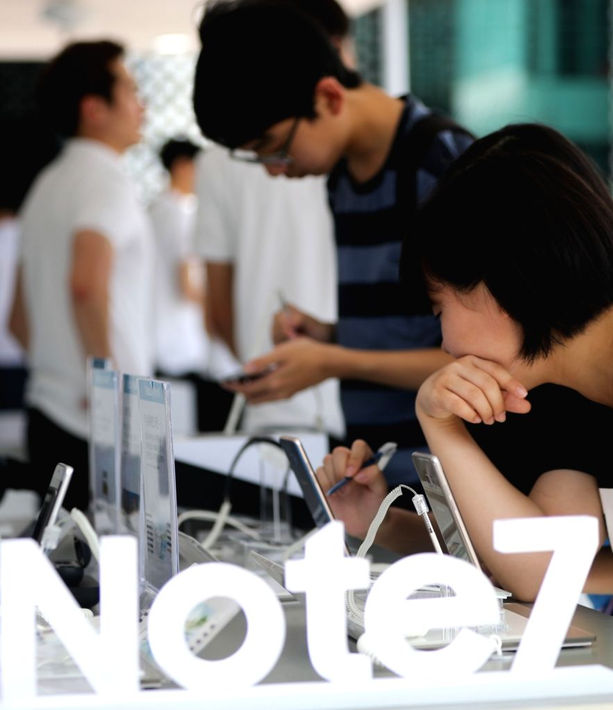 People try out Samsung latest high-end smartphone, the Galaxy Note 7, at an experience booth in a Seoul convention center on Aug 5, 2016.