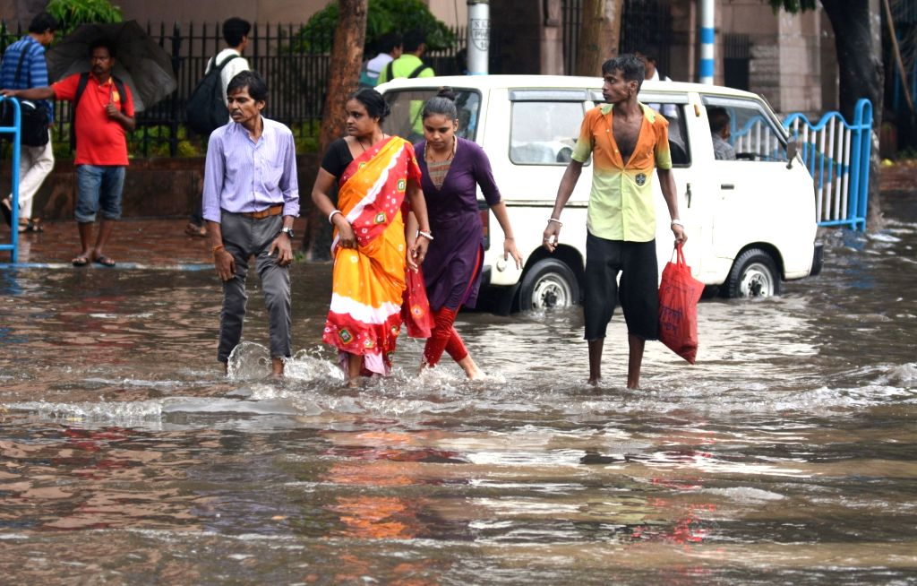 People try to cross a water-logged road after rains, in Kolkata on July 16, 2019.